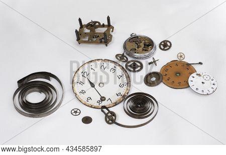 Disassembled Parts Of An Antique Clock, Clock Hands, Gear Wheels, Torsion Springs, Clock Faces, Scra