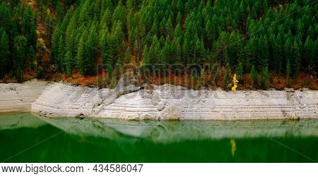 Lakeside lake forest forrest in mountains by water reflections of Autumn fall trees