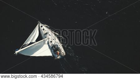 Top down of white sailing yacht on black water of ocean bay aerial. Nobody nature seascape at summer dusk day. Luxury yachting at open sea. Dramatic scenery of ship cruising at drone shot