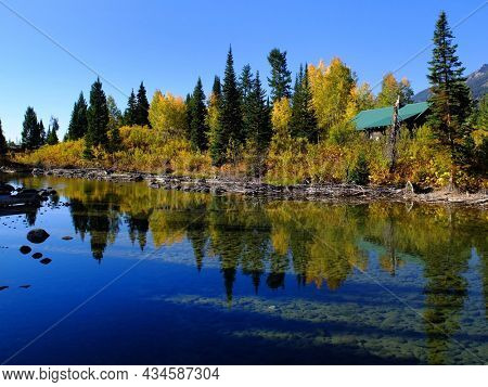 Old cabin in forest of trees in Autumn fall by river water reflections