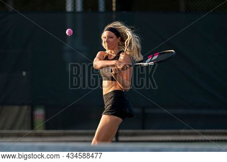 A gorgeous blonde model plays tennis in the afternoon sun on a tennis court
