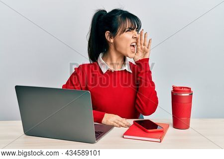 Young brunette woman with bangs working at the office with laptop shouting and screaming loud to side with hand on mouth. communication concept.