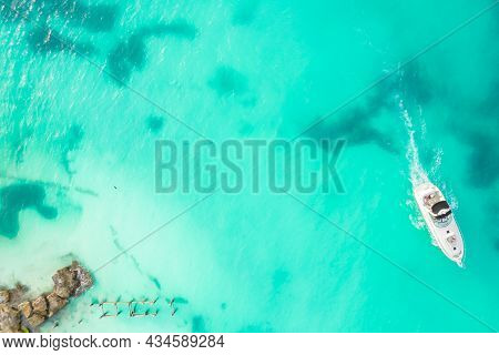 Amazing Top View Of Yacht. Aerial View Of Luxury Floating Small Ship In Blue Caribbean Sea. Yacht At