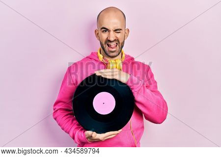 Young bald man holding vinyl disc winking looking at the camera with sexy expression, cheerful and happy face.