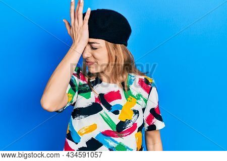 Young caucasian woman wearing french look with beret surprised with hand on head for mistake, remember error. forgot, bad memory concept.