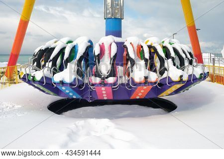 Amusement Park. Empty Abandoned Colorful Carousel Covered With Snow At Winter Time