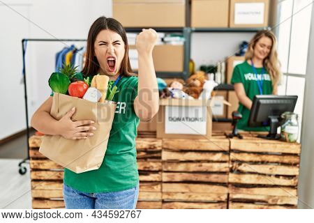 Young brunette woman at wearing volunteer t shirt holding bag with food annoyed and frustrated shouting with anger, yelling crazy with anger and hand raised