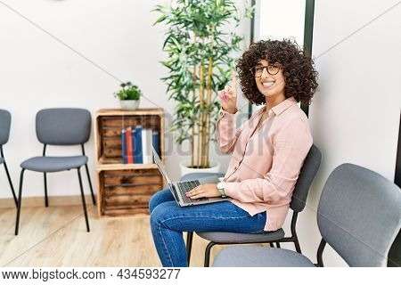 Young middle eastern woman sitting at waiting room working with laptop surprised with an idea or question pointing finger with happy face, number one