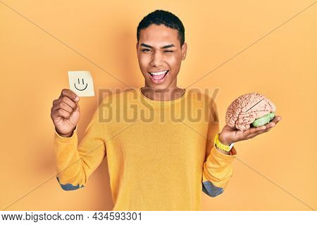 Young african american guy holding smile reminder and brain winking looking at the camera with sexy expression, cheerful and happy face.