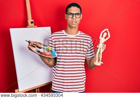 Young african american guy holding painter palette and art manikin in shock face, looking skeptical and sarcastic, surprised with open mouth