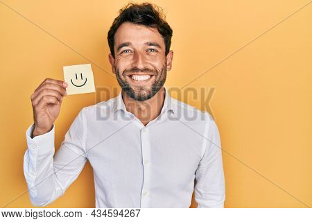 Handsome man with beard holding smile emoji reminder looking positive and happy standing and smiling with a confident smile showing teeth