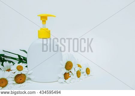 White Plastic Bottle With Dispenser On Light Background With Chamomile Flowers With Empty Space For