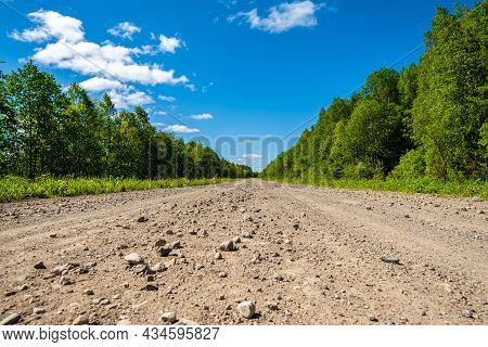Dirt Road Leading To Rural Settlements. Country Road And Bright Blue Sky.
