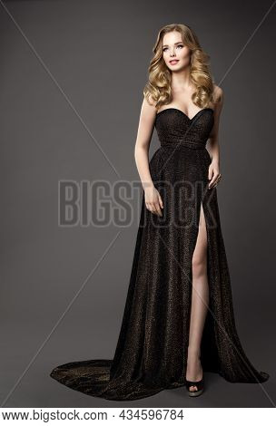 Elegant Fashion Woman In Black Dress. Glamour Model In Evening Shiny Gown With Split. Beauty Blonde