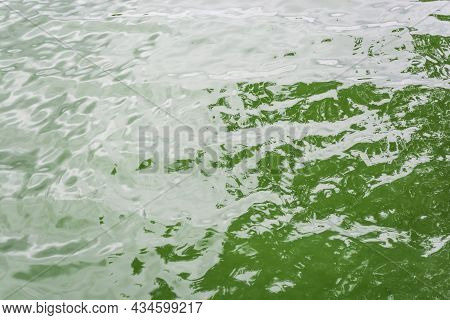 Small River Waves Of Green Hue, Shining In The Sun At Noon.