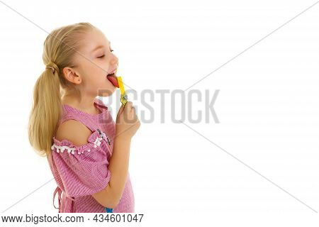 Cute Little Girl With Great Pleasure Licks A Candy. Happy Childhood Concept. Isolated Over White Bac