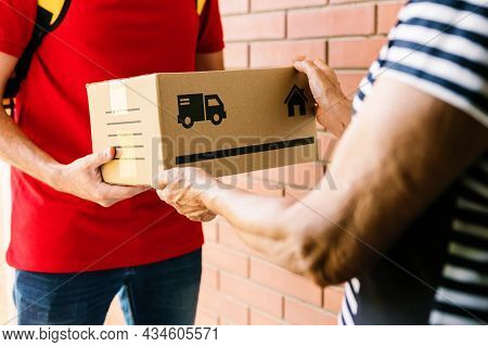 Postman In Red Uniform Delivering Package To Costumer - Senior Woman Receiving A Parcel At The Door