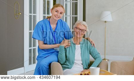Smiling young blonde nurse in uniform takes care of senior woman sitting in comfortable armchair in light room