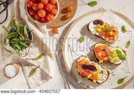 Italian Bruschettas With Roasted Tomatoes, Cream Cheese, Pineapple Slices And Herbs On A Kitchen Cou