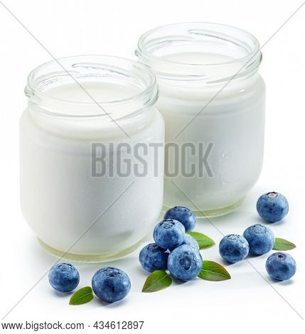 Two glass containers with plain yoghurt and berries isolated on white background.