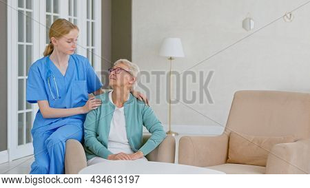 Smiling blonde nurse in uniform takes care of senior woman in light room at assisted living
