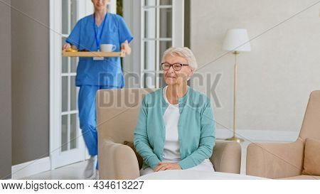 Blonde nurse in blue uniform carries breakfast and sits down near old lady patient in comfortable armchair