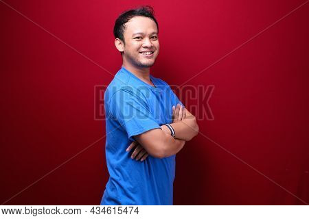 Portrait Of Smiling Young Asian Man Wearing Black Shirt Isolated On Red.