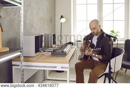 Talented Musician Playing Acoustic Guitar And Writing New Music In His Home Studio