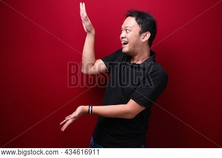 Smile And Happy Young Asian Man Is With Hand Point On Empty Space