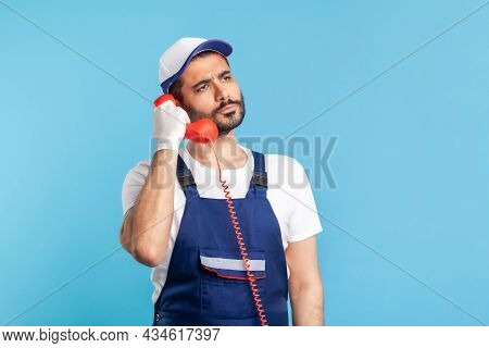 Housing Maintenance Call Centre. Attentive Handyman In Overalls, Safety Gloves, Holding Retro Phone