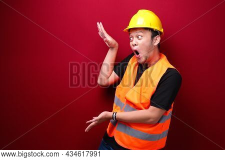 Young Asian Man Worker Is Surprised And Shouting Wow With Pointing Right With His Hand Isolated On R