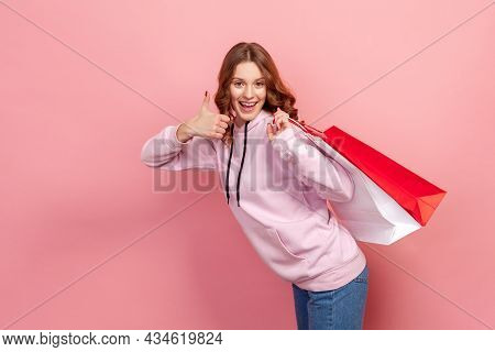 Portrait Of Smiling Brunette Teenage Girl In Hoodie Holding Shopping Bags Behind Back And Showing Th