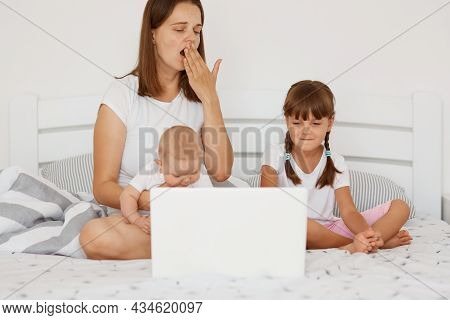 Portrait Of Tired Sleepy Woman Mother Sitting On Bed With Her Children And Working On Laptop, Yawnin
