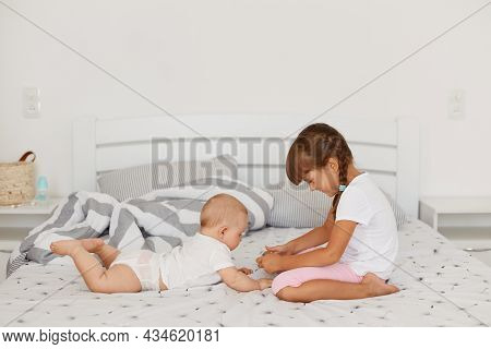 Little Cute Girl Wearing White T Shirt And Pink Shorts Playing With Her Little Infant Sister While B