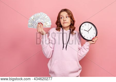 Portrait Of Pensive Curly Haired Teenage Girl In Casual Hoodie Holding Bunch Of Dollar Banknotes And
