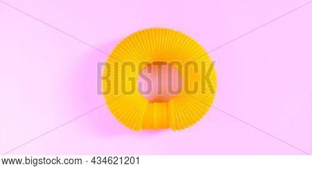 Pop Tube. Yellow Anti Stress Sensory Plastic Toy For Children On Pink Background. Fidget Corrugated