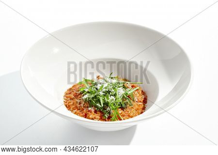 Vegan tomato risotto with rucola on white plate. Italian dish - veggie risotto isolated on white background. Plant based dining. Clean eating in restaurant menu. Eat less meat. Vegetarian lunch