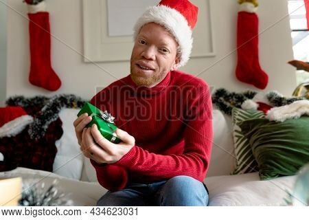 Albino african american man wearing santa hat making video call with christmas decorations. christmas, festivity and communication technology festivity and communication technology.