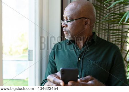 Thoughtful african american senior man holding smartphone ale looking outside window. retirement lifestyle and relaxing at home.