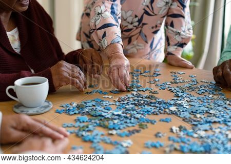 Hands of two diverse senior women and african american male friend doing puzzles. socialising with friends at home.