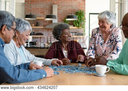 Group of diverse senior male and female friends doing puzzles at home. socialising with friends at home.