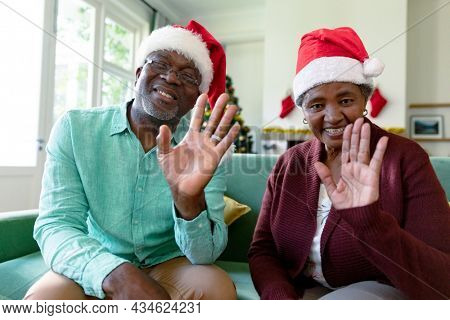 Happy african american senior couple wearing santa hats having video call at christmas time. christmas, festivity and communication technology.