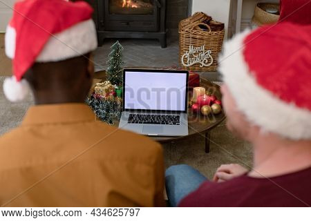 Back view of diverse men in santa hats using laptop with copy space on screen at christmas time. christmas, festivity and communication technology.