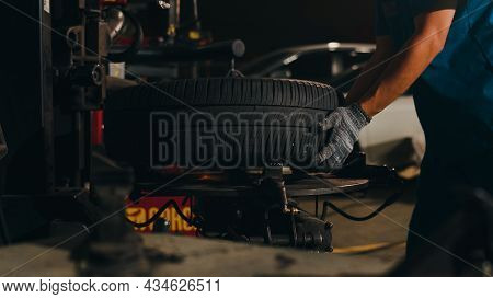 Professional Car Mechanic Changing A Car Tire On Lifted Automobile At Repair Service Station. Wheel