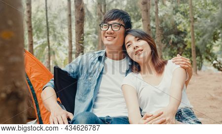 Young Asia Campers Couple Sitting In Chairs By Tent In Forest. Male And Female Traveler Relaxing And