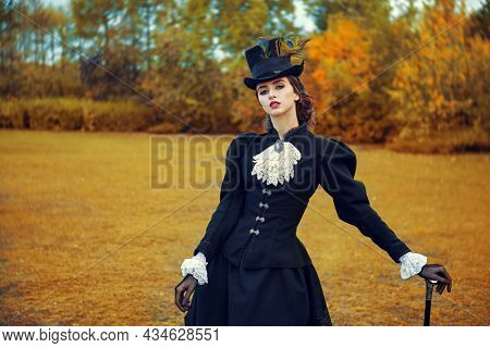 A confident and sophisticated lady in a strict black suit of the 19th century stands against the backdrop of an autumn park.