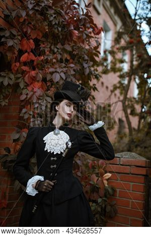 Vintage portrait of a beautiful exquisite lady of the 19th century standing by the autumn hedge. Historical reconstruction of the late 19th and early 20th century.