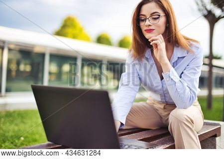 Cheerful Young Redhead Caucasian Woman Using Laptop At Outdoors In City Park