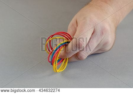 One Mans Hand Holds The Rubber Bands. A Group Of Multi-colored Round Rubber Bands On A Gray Backgrou