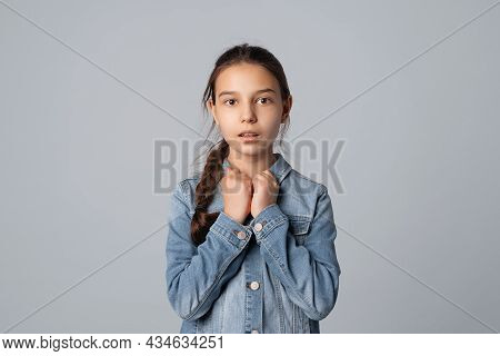 Preteen Girl Looking At Camera With Nervous And Scared Facial Expression, Isolated On Grey Backgroun
